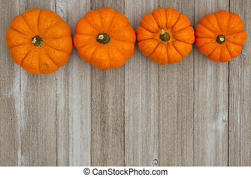 Autumn background with pumpkins on weathered wood