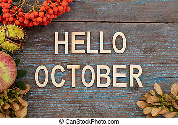 Autumn background with the text - Hello October on old wooden table