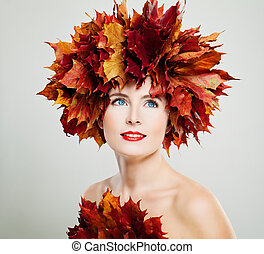 Autumn Beauty. Autumn Woman Smiling. Fashion Model with Red Fall Maple Leaves Wreath and Makeup