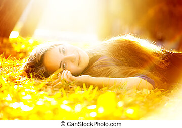 autumn beauty - beautiful woman in sunbeam lying on the ...
