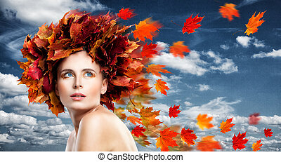 Autumn Beauty. Perfect Woman Fashion Model with Blowing Fall Leaves and Golden Makeup on Blue Sky Background