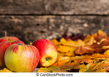 Autumn border from apples and maple leaves on wooden background