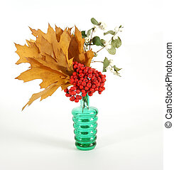 Autumn Bouquet with ash and oak leaves in a vase with colored glass on a white background