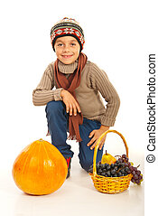 Autumn boy with pumpkin and grapes