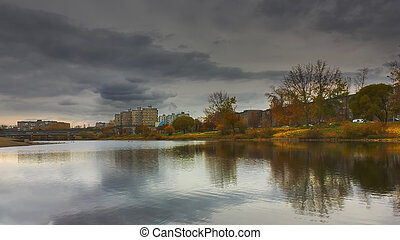 Autumn city landscape trees with colorful foliage are reflected in the river against a cloudy sky lit by the rays of sunset.