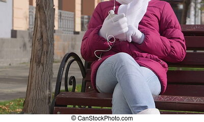 Autumn city scene girl listening music from smart phone on the bench