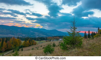 Autumn. Cloudy Sunrise over Mountain Village with Forest