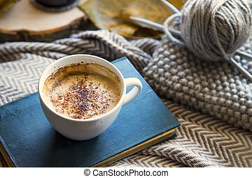 Autumn coffee cup with book and knitting wool and needles, cozy fall deco concept, home lifestyle warm coffee cup in autumn season