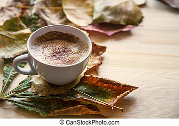 Autumn coffee cup with dried leaves decoration on wooden table, cozy fall deco concept, home lifestyle warm coffee cup in autumn season