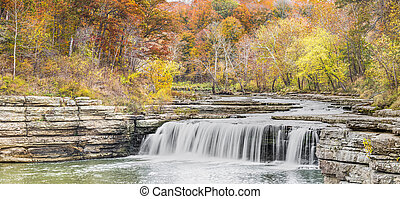 Lower Cataract Falls, a wide waterfall in Owen County, Indiana, plunges over a limestone cliff surrounded by colorful autumn foliage.