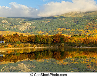Autumn colors reflected in the lake at sunset