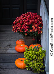 Autumn composition - bright orange pumpkins, colorful chrysanthemum potted, holiday front door steps decoration