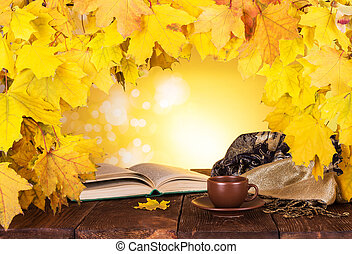 Autumn composition. Maple leaves, hot tea and a book