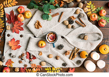 Autumn composition of ripe fruit, leaves, spices, candles, drink, nuts and cones