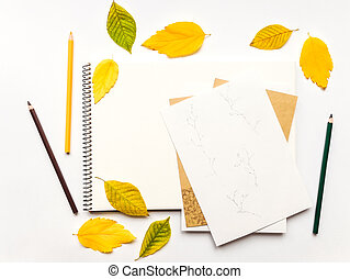 Autumn composition with album and pencils, decorated with yellow and green leaves. Flat lay, top view