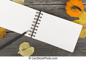 Autumn composition with blank open notebook