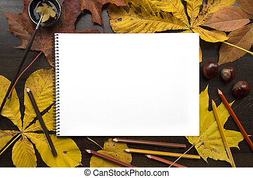 Autumn composition with empty album and fallen leaves