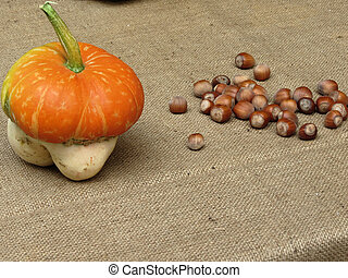 Autumn composition with pumpkin and hazelnuts on jute fabric background
