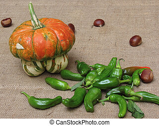 Autumn composition with pumpkin, green peppers and chestnuts on jute fabric background