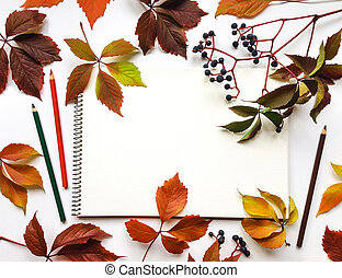 Autumn composition with sketchbook and pencils, decorated with red leaves and berries. Flat lay, top view