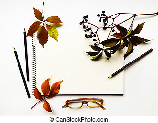 Autumn composition with sketchbook, pencils and glasses, decorated with red leaves and berries. Flat lay, top view