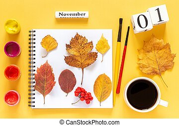 calendar November 1 cup of coffee, notepad with autumn colored leaves and watercolor paints on yellow