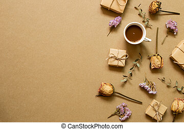 Autumn concept. Cup of coffee, gift boxes, dry rose, statice flowers, eucalyptus leaves on brown kraft paper background. flat lay, top view, copy space