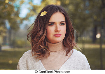 Autumn concept. Young brunette woman with fall leaf outdoor portrait