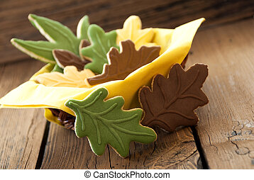 Autumnal Cookies in different Fall Colors in a small Cup on Wooden Planks