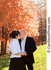 Autumn couple walking park and kissing. Autumn friends walk outdoor.
