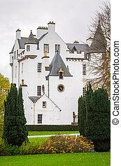 Big white castle. Small trees grow around the castle. Scotland. Autumn day.