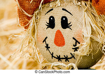 Autumn, fall decoration at pumplin patch featuing a scarecrow and wagon with straw