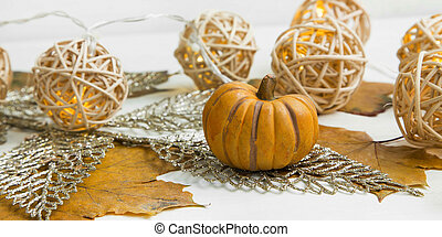 Autumn decorative pumpkin with lights and glitter leaves