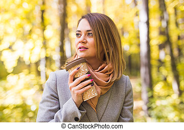 Autumn, drink and people concept- Close up portrait of young beautiful woman in grey coat with coffee