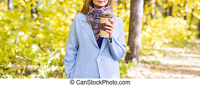 Autumn, drinks and people concept - Cup of hot drink in woman's hand