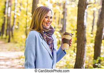Autumn, drinks and people concept - Woman holding cup of hot drink