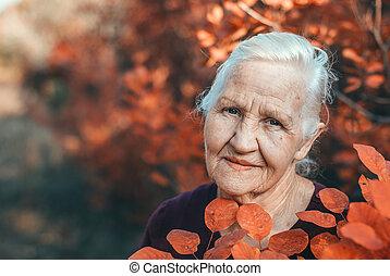 Autumn elderly woman outdoor