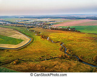 Autumn evening rural aerial view with river, creek, brook, village