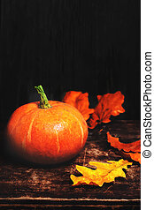 Autumn Fall background with pumpkins and golden leaves on rustic wooden background. Happy Thanksgiving Card with copy space.