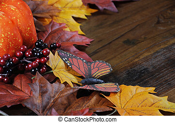 Autumn Fall background with red, brown and yellow leaves, orange pumpkin and monarch butterfly on dark recycled rustic wood table - angle close up.