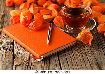 Autumn (fall) still life with cup of tea, colorful leaves over rustic wooden background.