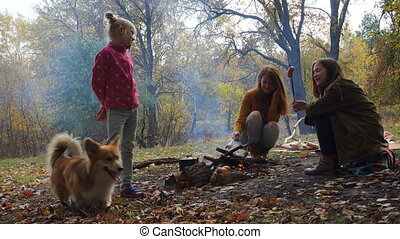 autumn family picnic - smiling mother, daughters and dog on...