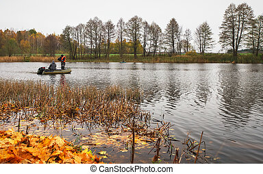 Autumn fishing. Fall reflections in a lake with a boat