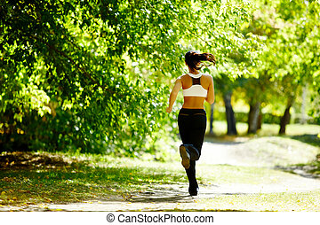 Autumn fitness - A young girl jogging in the park