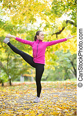 Autumn fitness outdoors: Extended Hand to Big Toe pose -...