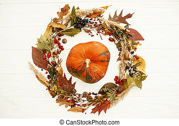 Autumn Flat Lay. Happy Thanksgiving. Pumpkin in beautiful fall leaves wreath with berries,nuts,acorns, herbs on rustic white background top view. Seasons greetings card mockup