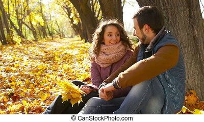 Autumn Flirt - Flirty couple cuddling by the tree in the...