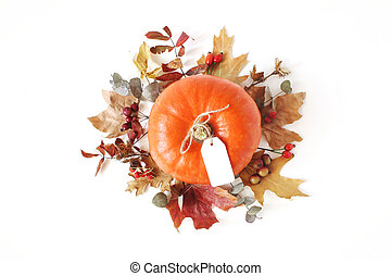 Autumn floral composition with orange pumpkin. Wreath made of dry maple, eucalyptus leaves and berries on white table background. Fall, Halloween and Thanksgiving design. Flat lay, top view.
