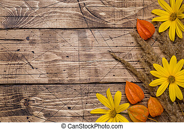 Autumn flowers on wooden background with copy space.