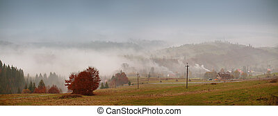 Autumn fog in mountain village. Cloudy rainy misty autumn
